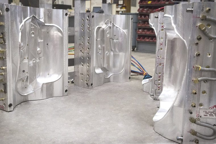 Two blow molding molds sitting on ground, open.
