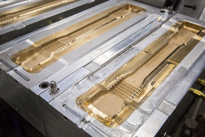 A multi-cavity blow molding mold for seat belt sleeves.