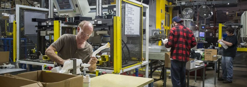 Two men working on blow molded products at the Regency Plastics manufacturing facility.