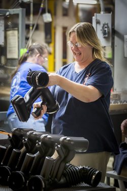 A woman inspects a blow molded part that has been welded.