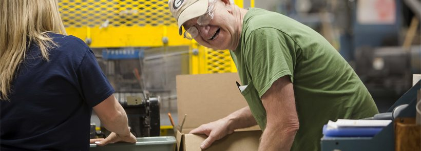 A man enjoying himself as he packs extruded plastic components for delivery.