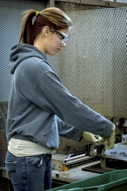 A woman assembling a two-shot injection molded part.
