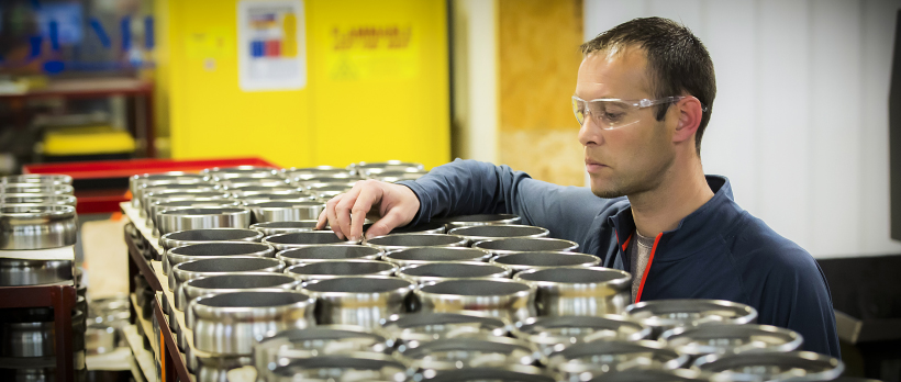 A production machining engineer inspects finished parts.