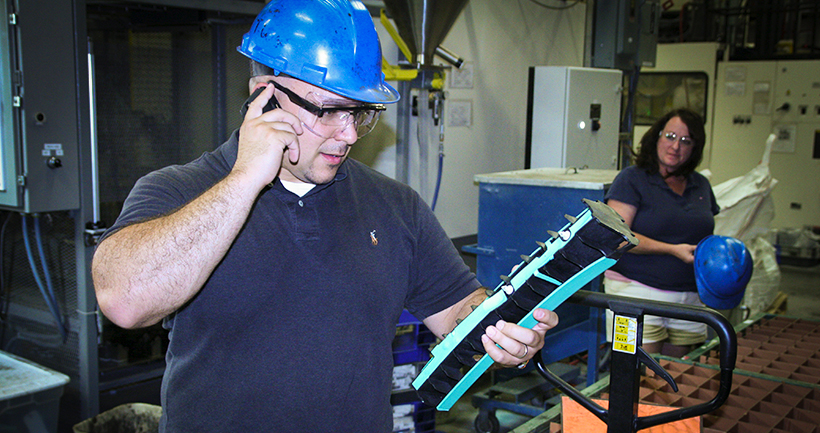 A man inspects a two-shot molded part for defects.
