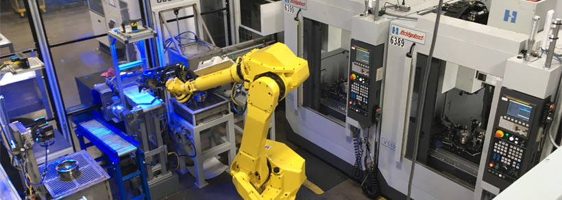 An overhead view of a fully-automated metal machining cell with robotics.