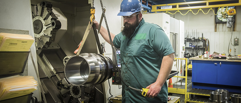 A man using a crane to lift a large part out of a precision CNC mill on the machine shop floor.