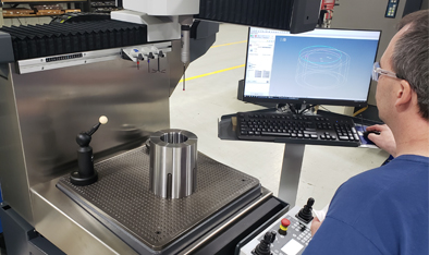 A man using a CMM machine to inspect a machined part.