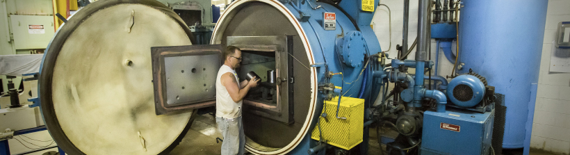 A man loading a machined part into a heat treat furnace.